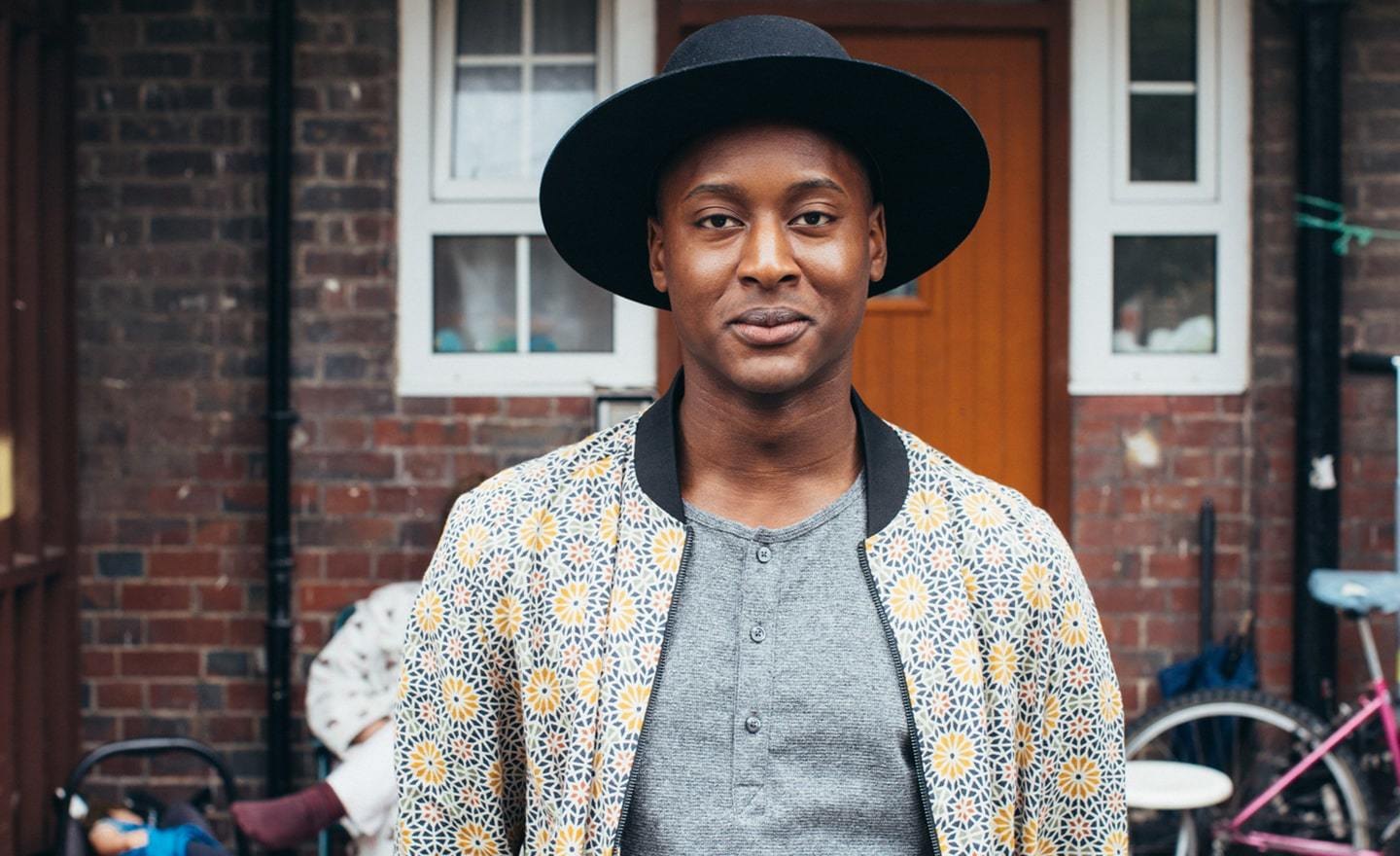 Black man in a hat smiling at camera