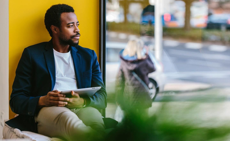 Black man seated in window sill