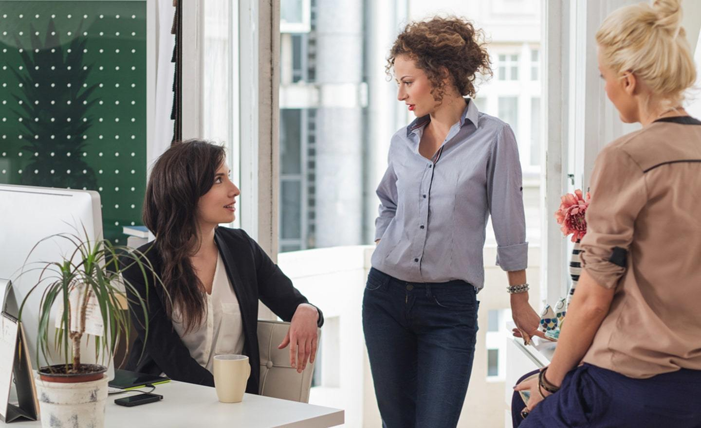Three women having a discussion in an open office