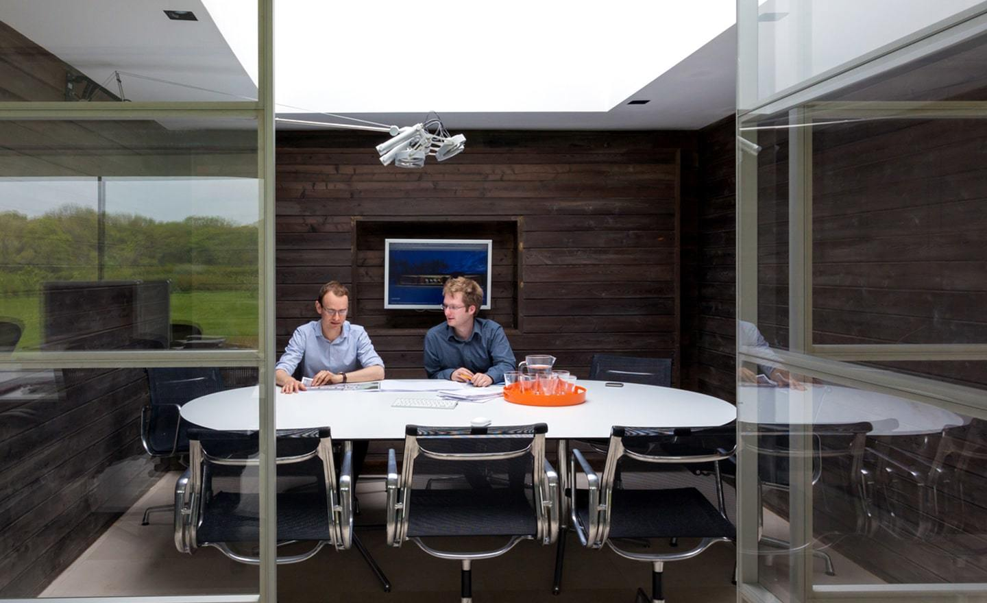 Two men sitting in a modern wood conference room