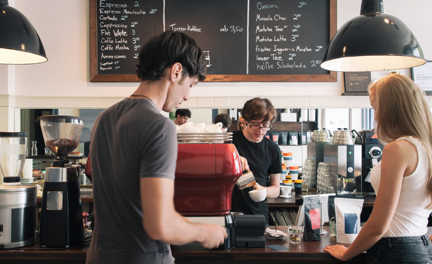 Two people buying coffee from a barista