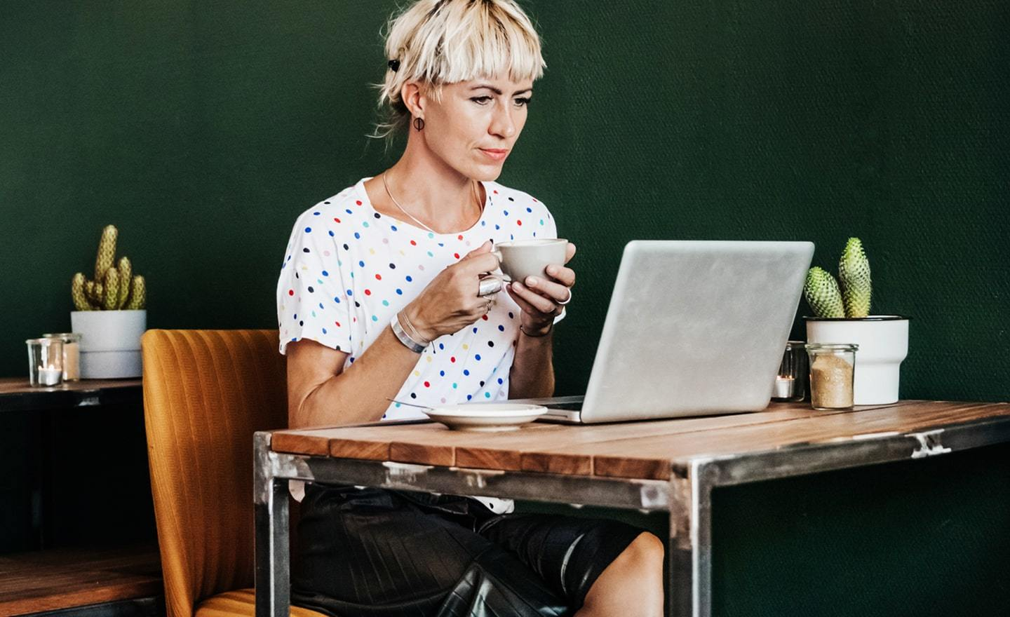 Woman working at a table with coffee r