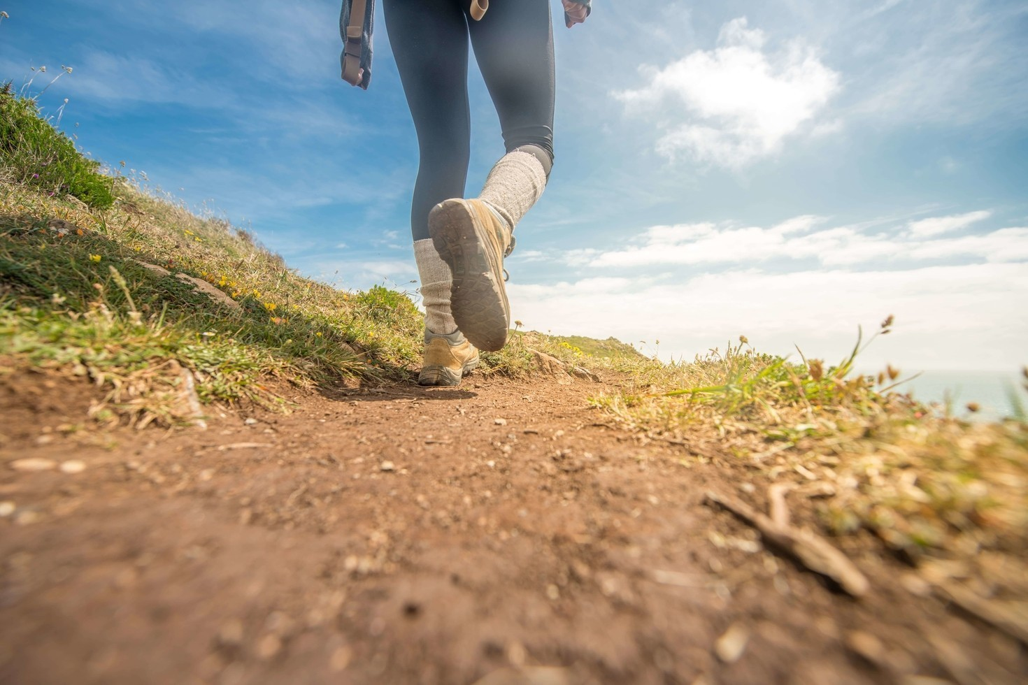 Girl Wearing Walking Boots Hiking Up A Mountain