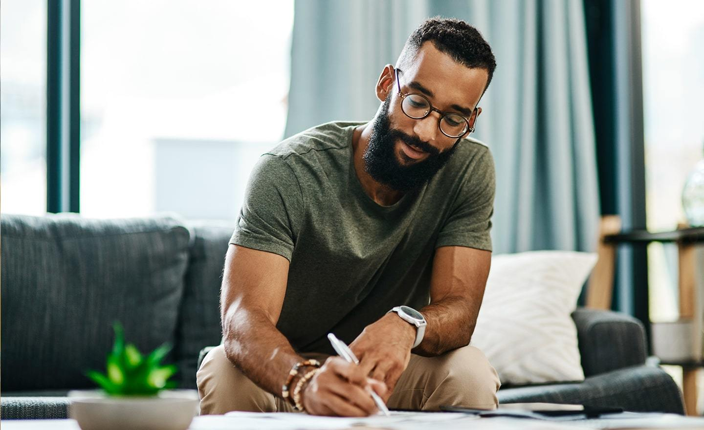 Man working from home writing notes