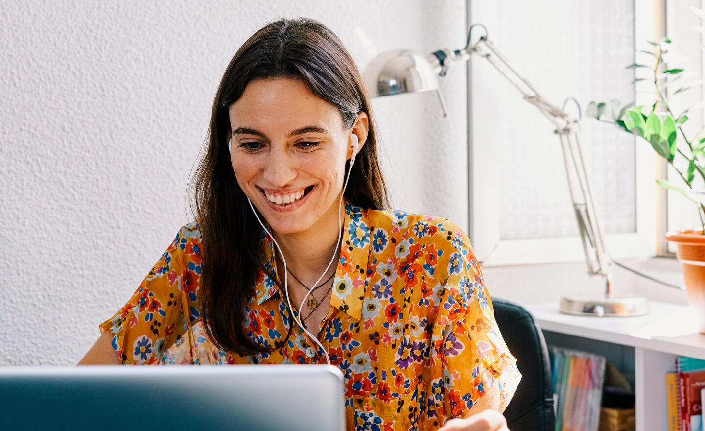 Woman in a flowered shirt working at a laptop