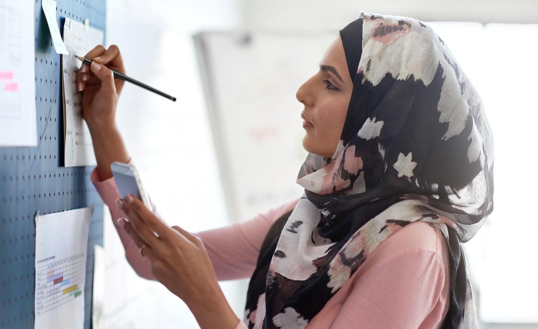Woman in headscarf writing on whiteboard